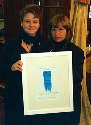 Gaelle Mellis and another woman stand and display their award.