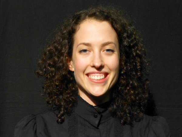 Felicity Doolette is a dancer and performer with Restless Dance Theatre. She is a striking young woman with dark brown very curly hair that falls to her shoulders. She is pictured against a black background and wears a high necked black blouse. She has a charming broad smile.