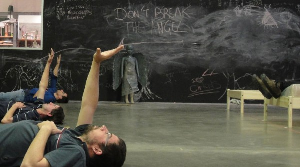 Three men lie on a concrete floor with their right arms raised. A chalkboard crosses the background covered in smudged comments. A small, grey statue of an Angel stands against the chalkboard.