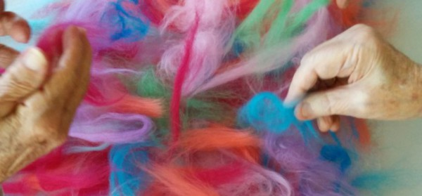A photograph of two hands rummaging through a pile of tifts of hair in a variety of colours.