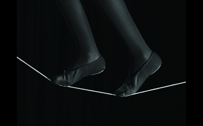 A black and white image of a pair of feet balanced on a white tightrope that transects the photograph.