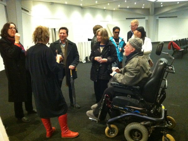 Jo Verrent speaking with audience members following her forum in Adelaide. Jo is wearing red boots, standing with her back to the camera.