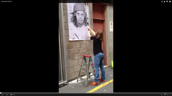 A screen shot from the YouTube video of Chris Dyke pasting up his portrait poster