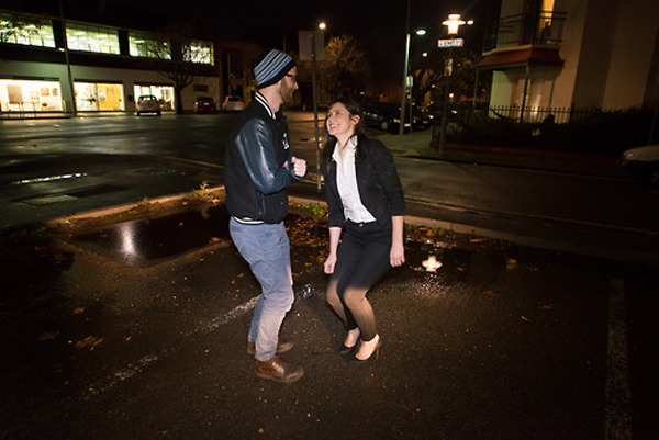 A man and a woman are dancing on the footpath of an empty street. It is nightime and they are lit by streetlamps and the flash from the photographer's camera.