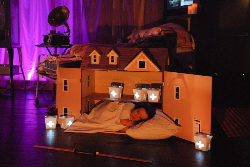A short-statured woman sleeps in front of a dollhouse filled with white boxes, lit from within by glowing lights.
