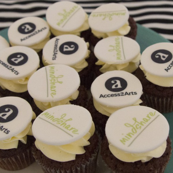 A plate full of small brown cupcakes each with white frosting and carrying small white candy disks printed with either the logo for Access2Arts or mindshare