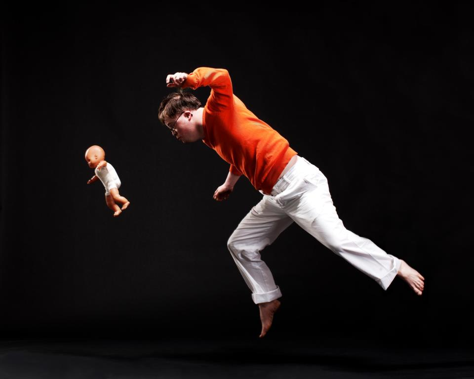 Lorcan jumping through the air with a doll. in colour, Photo credit Katie Pashley.
