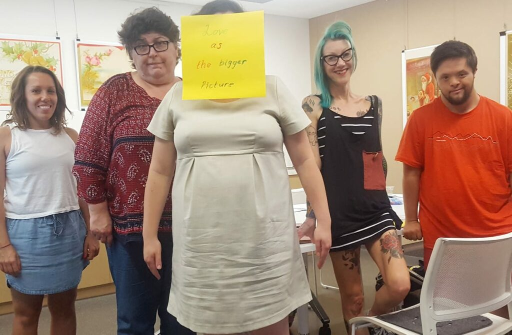 Five people standing smiling at the camera. The person in the centre has a post it note over her face that says love as the bigger picture.