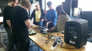 Artist in residence, Liz Martin, and participants stand around the table piled with accessible music technology.