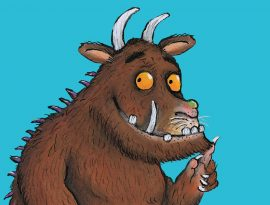 An illustration of The Gruffalo, a large creature with dark brown fur, orange eyes and big white teeth and horns.