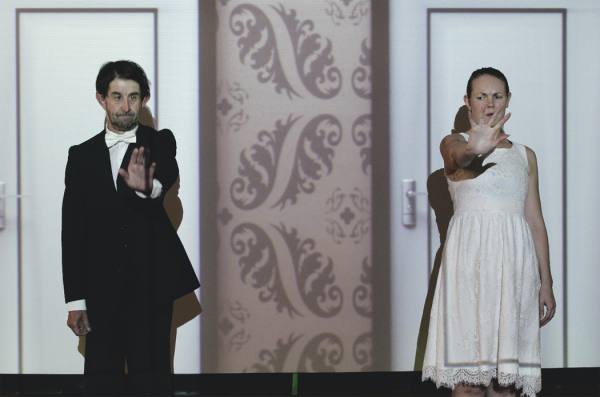 A man wearing a black tuxedo and a woman dressed in a white dress stand centre stage facing the audience, each with an arm outstretched and a palm raised as though stopping or halting an approacher. Behind them is a projection of a wall with two doors.