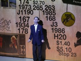 A man dressed in a black tuxedo stands facing the audience. Behind him is a projection of numbers, prices, a television and the logo for the SANFL team, the Glenelg Tigers.