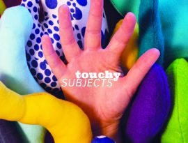 A hand emerges from tactile handmade artwork in many colours and patterns